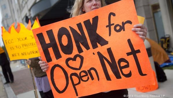 A demonstrator outside the Federal Communications Commission headquarters shows her support for strong net neutrality regulations.