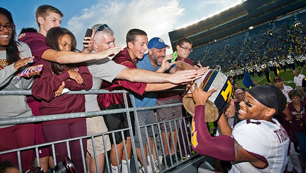 Minnesota fans celebrate with players after the Gophers' win in Michigan Stadium last season.