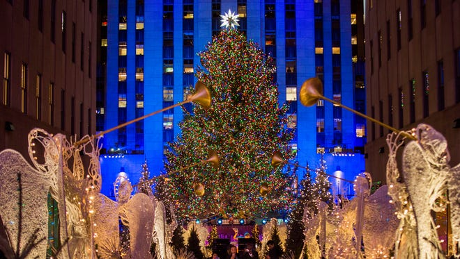 The Rockefeller Center Christmas tree stands lit as people take photos of it and the holiday decorations at Rockefeller Center during the 85th annual Rockefeller Center Christmas tree lighting ceremony, Nov. 29, 2017, in New York.
