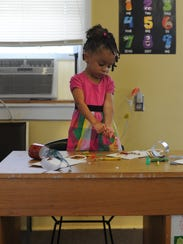 Jasiah Rosario, 3, paints and decorates a craft bag