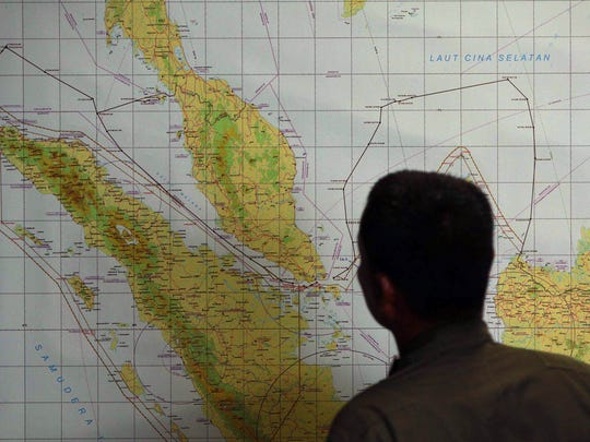 A member of the Indonesian Air Force  inspects the military search operation for the missing Malaysian Airlines flight MH370 on March 12, 2014 in the area of Malacca Strait, a sea passageway between Indonesia (seen left of the map) and Malaysia (seen top left of the map). Malaysia faced a storm of criticism on March 12 over contradictions and information gaps in the hunt for a missing airliner with 239 people on board, as the search zone dramatically veered far from the intended flight path.