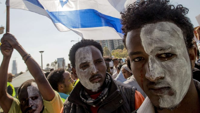 African asylum seekers, who entered Israel illegally via Egypt, wave an Israeli national flag as they take part in a protest in front of the Interior Ministry in the Mediterranean coastal city of Tel Aviv on Feb. 11, 2014, after several days of mass protests against Israel's immigration policies. The migrants, primarily from Eritrea and Sudan, marched from downtown Tel Aviv to the embassies, calling for help in the face of Israel's refusal to give them refugee status and its detention without trial of hundreds of asylum seekers.