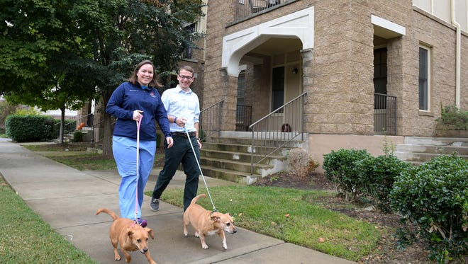 Kelly Wolenberg Harris and her husband Nick Harris walk their dogs, Brandy and Maxwell outside condominium complex near West End Ave. on Thursday, Oct. 27, 2016.   Kelly's parents bought the condo when she was in medical school.
