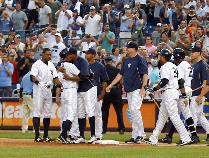 New York Yankees right fielder Ichiro Suzuki  is congratulated by teammates after recording his 4000th hit against the Toronto Blue Jays at Yankee Stadium.