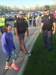 From left, 9-year-old Meghan Spence; her father, Matt Spence, a sergeant with the Sheboygan County Sheriff's Office; and Andy Jacobs, a trooper with the Wisconsin State Patrol, get ready for the Run with the Cops 5K Run/Walk to support local Special Olympics Wisconsin athletes in De Pere on Thursday night, May 5, 2016.