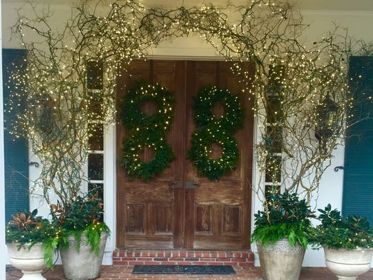 Magnolia leaves fill urns which flank rustic wooden doors hung with greenery in the infinity symbol while bare branches entwined with tiny white lights frame the setting.