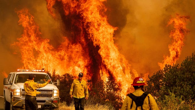 Flames from the LNU Lightning Complex fires leap above Butts Canyon Road on Sunday, Aug. 23, 2020, as firefighters work to contain the blaze in unincorporated Lake County, Calif.