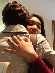 Nikita Deep, 16, embraces a family friend at Antigo