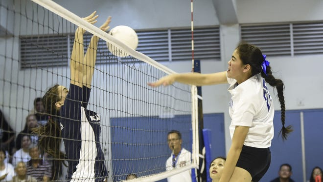 Notre Dame Royals' Sheri Stanley blasts a kill shot off an Academy of our Lady of Guam Cougars blocker's hands for a first set point in an Independent Interscholastic Athletic Association of Guam Girls' Volleyball League game at ND on Sept. 29.