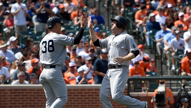 New York Yankees' Rob Refsnyder (38) high-fives Chase Headley, right, after they scored on a single by Austin Romine during the first inning of a baseball game against the Baltimore Orioles, Sunday, Sept. 4, 2016, in Baltimore.