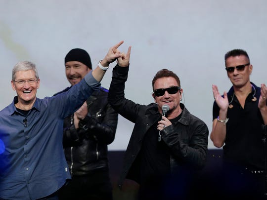 AP Apple CEO Tim Cook, left, smiles next to U2 during