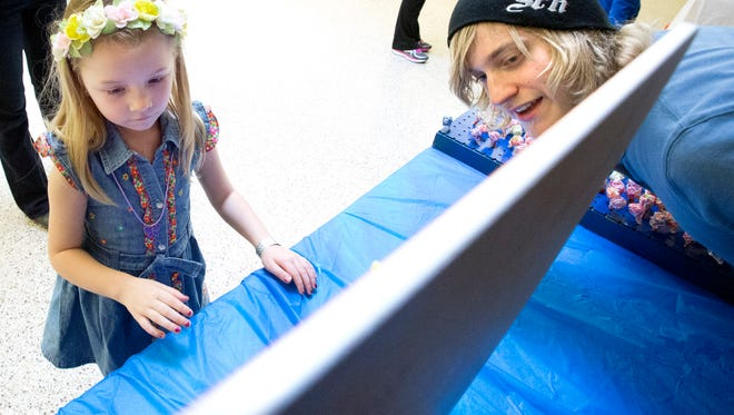 Quinn Cahlamer (left) watches for the result in the Spin-a-Prize game run by Jacob Pflughoeft at Menomonee Falls High School's 2016 Winter Carnival. This year's carnival is Sunday, Feb. 25.