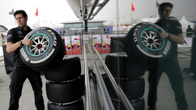 A Mercedes crew member prepares tires outside the team's garage at Shanghai International Circuit on Thursday.