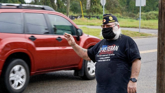 Joe Shores waves to those passing by American Legion Post 505 on Wednesday, November 11, 2020.