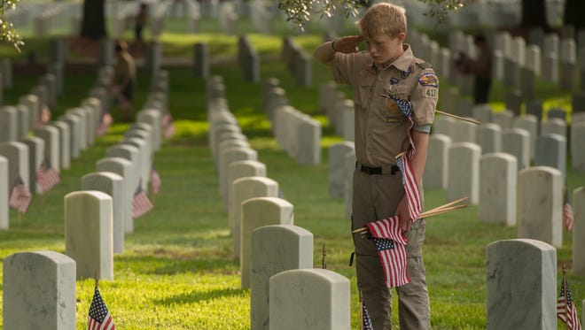 Sam Linkous of Troop 417 salutes after placing a flag at a grave marker May 26 during the Memorial Day Flag Placement at Barrancas National Cemetery.
