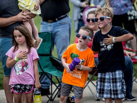 Kids wait with their hands on their hearts to watch