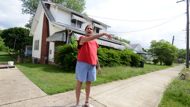 Therese Brunton stands outside a house next to her home in the 500 block of West Wheeling Street in Lancaster. Brunton has complained to the city and her city council representative about the state of the house and yard.