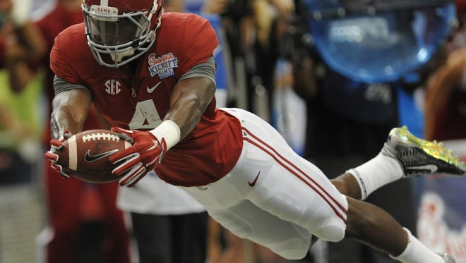 Alabama running back T.J. Yeldon dives for a first-half touchdown against West Virginia at the Chick-fil-A Kickoff Game at the Georgia Dome in Atlanta. Alabama running back T.J. Yeldon (4) dives for a first half touchdown against West Virginia at the Chick-fil-A Kickoff Game at the Georgia Dome in Atlanta, Ga. on Saturday August 30, 2014.