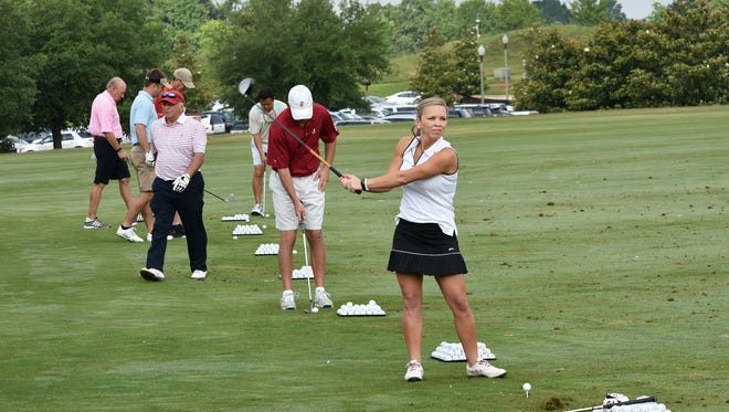 Lindsey Smith, foreground, prize winner for the Longest Putt at hole #18, practiced with other players before MACOA's Swinging Fore Seniors Golf Classic commenced on the RTJ Golf Trail (Courtesy of David Rose Designs)