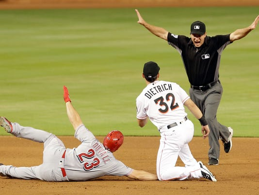 Cincinnati Reds' Adam Duvall (23) is called safe by second base umpire Ben May, right, as Miami Marlins second baseman Derek Dietrich (32) looks at May after Duvall hit a base hit in the fourth inning of a baseball game, Friday, July 8, 2016. (AP Photo/Alan Diaz)