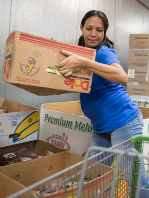 Yoandra Diaz Cabrera helps distribute food at the St. Mary's Food Bank Alliance on Thursday, July 13, 2017, in Phoenix, Ariz.