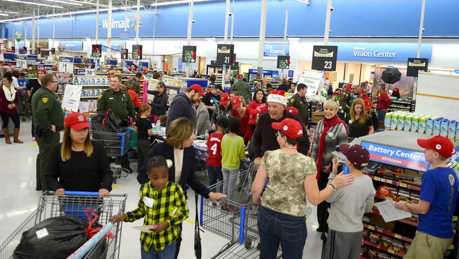 A crowd shops at a Walmart Supercenter during the holiday season. Walmart announced Jan. 15, 2016, that it is closing 269 stores worldwide, including 154 in the U.S.