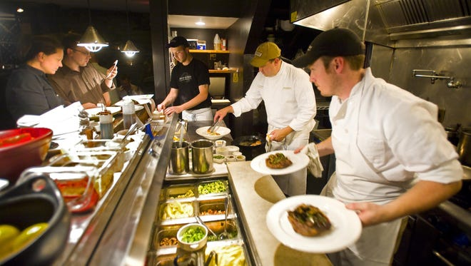 Chef Eric Warnstedt (center) plates a meal during the dinner rush at the Hen of the Wood restaurant in Waterbury on Friday August 7, 2009.