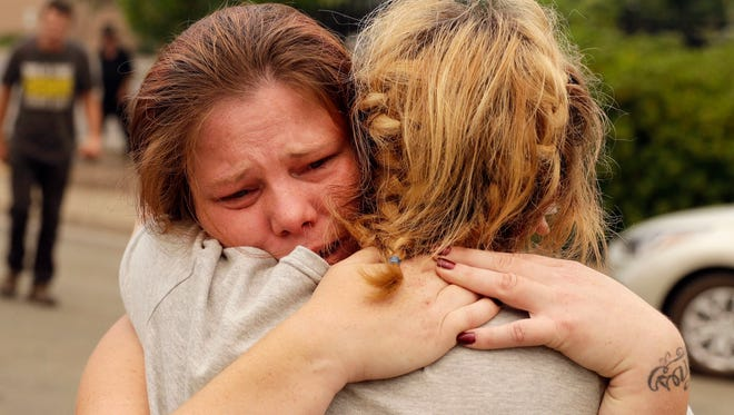 Carla Bledsoe, facing camera, hugs her sister Sherri outside of the sheriff's office after hearing news that Sherri's children James, 4, and Emily 5,  and grandmother were killed in a wildfire Saturday, July 28, 2018, in Redding, Calif.
