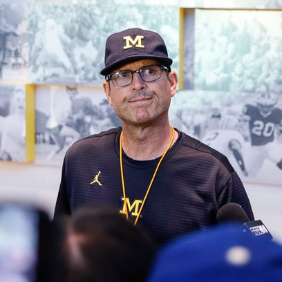 Michigan Wolverines coach Jim Harbaugh speaks with