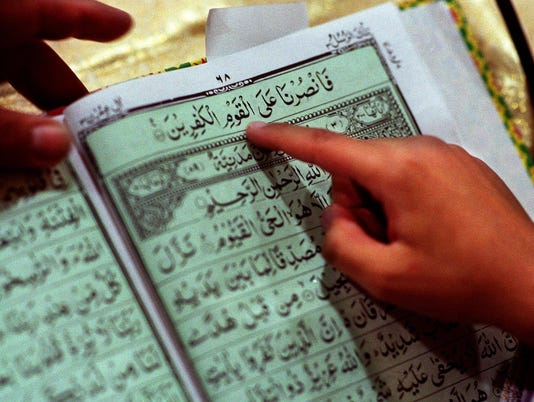 Text: 2000.0401.05.2--Islam1--Mohsin Sulton, 8, reads several passages of the Quran in arabic as part of the Ameen ceremony when a child reads the Quran in Arabic for the first time. photo by Steven M. Herppich/Cincinnati Enquirer