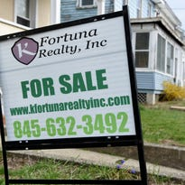 A for sale sign stands outside a home in the Village of Wappingers Falls.