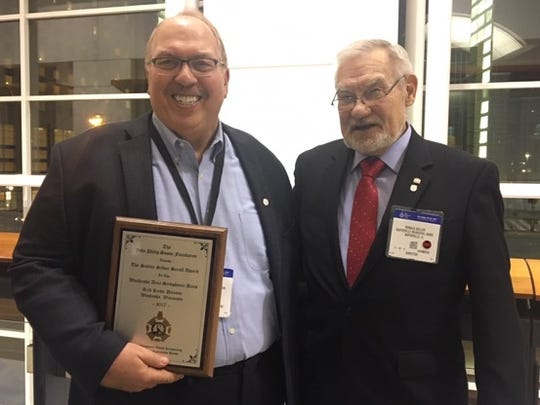 Rick Kirby accepts the Sudler Silver Scroll Award on behalf of the Waukesha Area Symphonic Band from Ron Keller at Midwest International Band and  Orchestra Directors Convention at McCormick Center, Chicago.