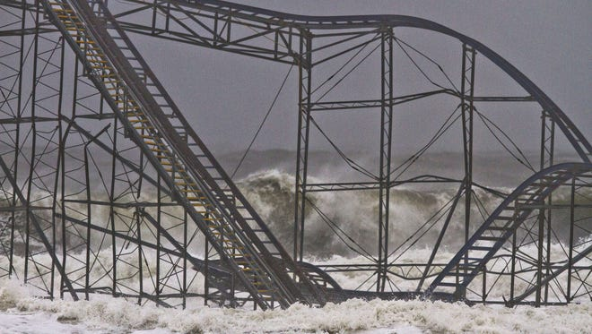 Waves crash into the Jet Star rollercoaster that sits in the Atlantic Ocean where Casino Pier was prior to superstorm Sandy.
