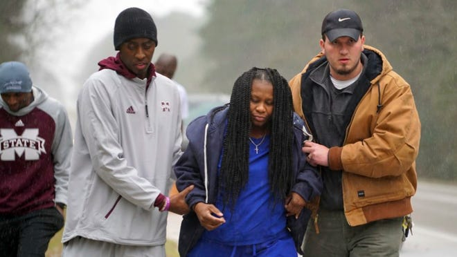 Mississippi State trainer Ryan Dotson, left, and an unidentified man aid a motorist who's car flipped over in front of the team bus in Mississippi, as they were heading to LSU for an NCAA college basketball game.