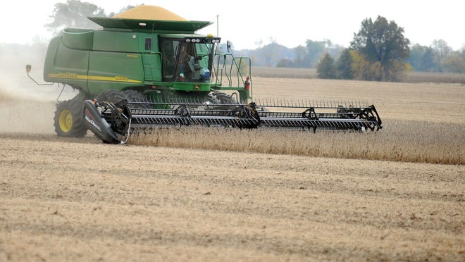 A combine harvests soybeans from a field along Patten Pike near Ohio 98 in October. Farm land values have gone up about 40 percent from 2010 to 2012.