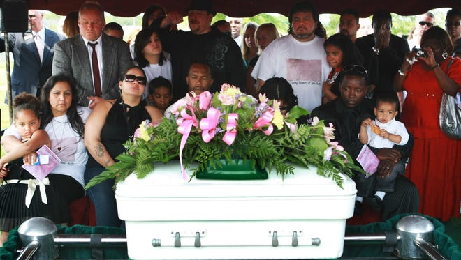 The family and friends of 2-year-old Jada Justice say final prayers before her casket is lowered to the ground on July 3, 2009, at Heritage Cemetery in Portage, Ind.