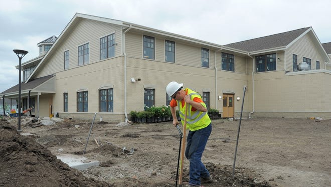 Workers wrap up construction work in 2015 before the St. Ann Center for Intergenerational Care opened its child and adult day care center in Milwaukee.