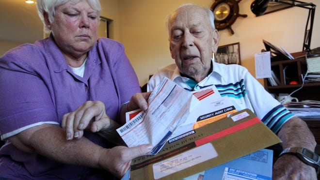 A woman sits with her father as she displays some of the scam mail he has received in an attempt to defraud him.