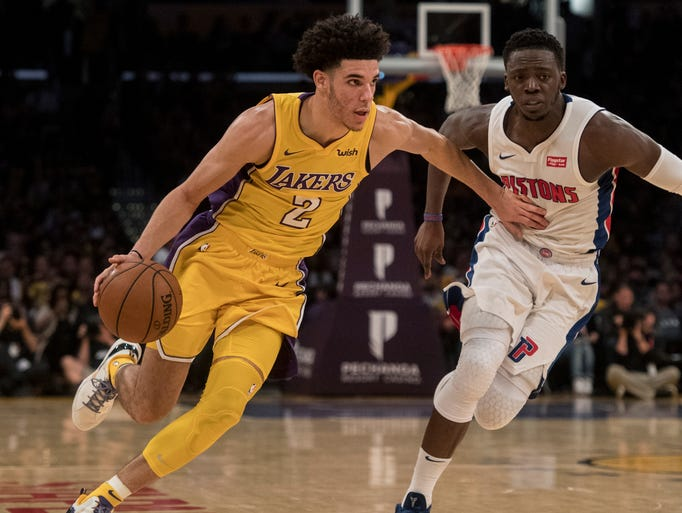 Lakers guard Lonzo Ball, left, drives past Pistons