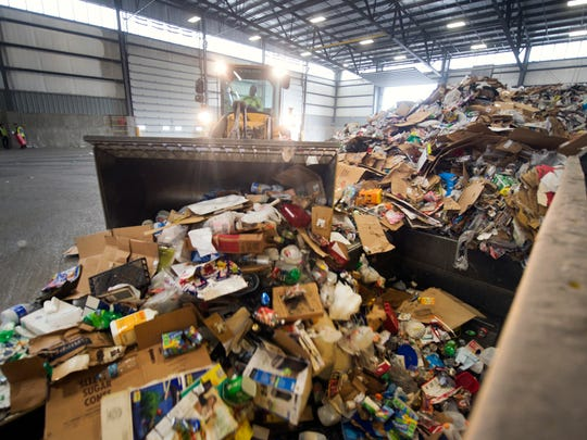 Recyclables are unloaded from a truck at Penn Waste's