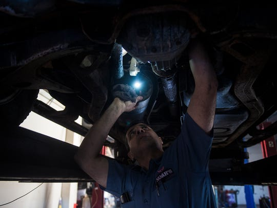 Owner Noah Desai checks underneath a vehicle at his Hanover business, Noah's Auto Sales & Service, on Jan. 19.