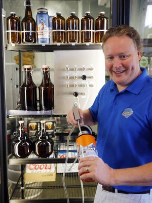 Arthur Rice, owner of I-35 Spirits in Ankeny demonstrates how his growler filling station will work starting July 1st. 2015.