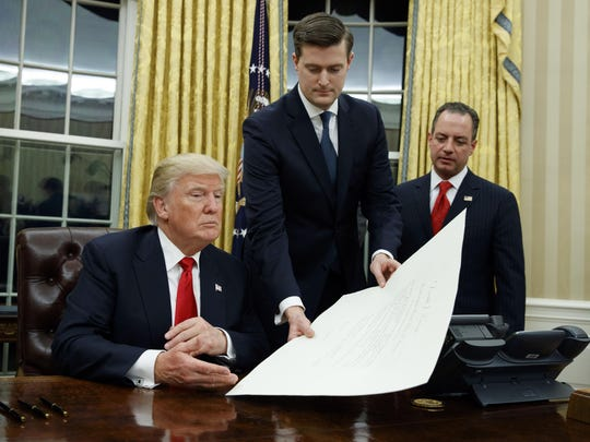In this Jan. 20, 2017 file photo, White House Staff Secretary Rob Porter, center, hands President Donald Trump a confirmation order for James Mattis as defense secretary, in the Oval Office of the White House in Washington, as White House Chief of Staff Reince Priebus, right, watches.