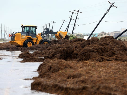 Crews clear debris from Highway 361 in Port Aransas on Saturday, Aug. 26, after Hurricane Harvey landed in the Coastal Bend area.
