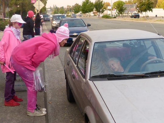Maggie Groves chats with a driver who stopped for a Think Pink Day bag outside the KIXE-TV offices Thursday on Market Street.