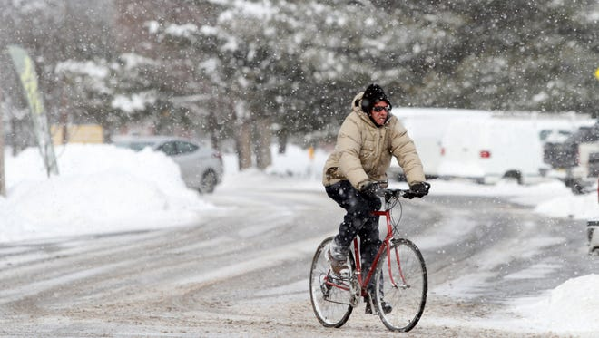 A man rides a bicycle in Jamesburg, Tuesday, after several inches of snow fell in Middlesex County.