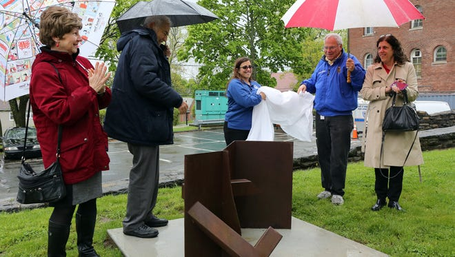"""Unveiling the sculpture from Ernest Shaw's """"Ruin"""" series are (from right) Solange De Santis, chair of the Village of Mamaroneck Arts Council, Michael Rosenbaum, the Arts Council member who donated the sculpture; Mamaroneck Village Recreation Superintendent Sandy Korkatzis; Mamaroneck Village Mayor Norman Rosenblum; and Mamaroneck Town Councilwoman Jaine Elkind Eney."""