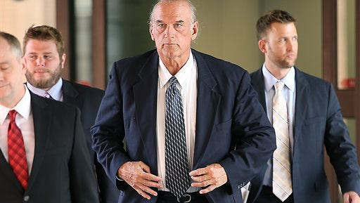 In this file photo former Minnesota Gov. Jesse Ventura, center, leaves federal court in St. Paul, Minn. Ventura, who was awarded $1.8 million in a defamation lawsuit against author Chris Kyle's estate, is suing HarperCollins saying publicity about the book and Kyle's claims about him generated millions of dollars in profits for the publisher.
