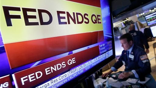 In this file photo, specialist Michael O'Mara works at his post on the floor of the New York Stock Exchange, as a television screen shows the decision of the Federal Reserve to end quantitative easing. Quantitative easing was designed to make bonds look more expensive to investors than stocks by artificially boosting bond prices.