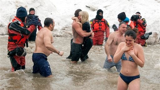 """Actor Taylor Kinney, center left, holds his fiancée, pop star Lady Gaga, as they and members of the """"Chicago Fire"""" cast take part in the Chicago Polar Plunge at North Avenue Beach on Sunday in Chicago."""